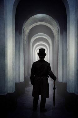 Jaroslaw Blaminsky SILHOUETTED VICTORIAN MAN IN PASSAGEWAY AT NIGHT Men