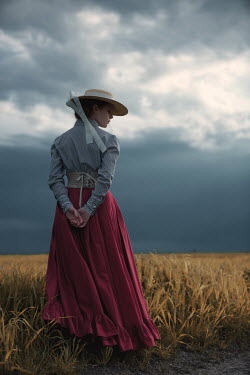 Magdalena Russocka historical woman in field with stormy sky Women
