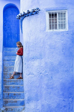 Holly Leedham WOMAN LEANING AGAINST BLUE BUILDING Women