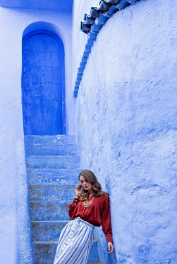 Holly Leedham WOMAN LEANING AGAINST TURQUOISE BUILDING Women