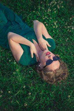 Joanna Czogala WOMAN WEARING SUNGLASSES  LYING ON GRASS Women