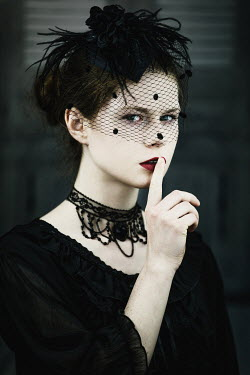 Magdalena Russocka young woman wearing black veil with finger on lips