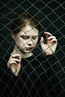 Magdalena Russocka young woman behind rope net