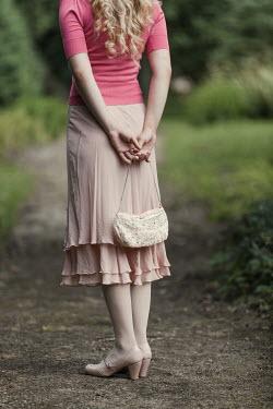 Magdalena Russocka close up of retro woman holding handbag in garden
