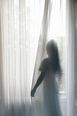 Eva Van Oosten WOMAN STANDING BEHIND NET CURTAINS Women