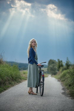 Magdalena Russocka young blonde woman with bike standing on country road