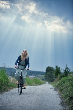 Magdalena Russocka young blonde woman riding bike on country road