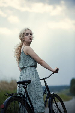 Magdalena Russocka young blonde woman with bike on country road