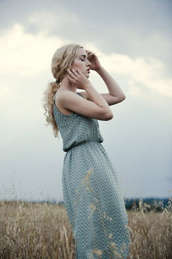 Magdalena Russocka daydreaming blonde woman standing in field
