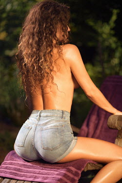 Alex Maxim Back of a sexy young woman with tanned wet skin and long hair, sitting topless on a lounge chair wearing high-waist denim shorts.