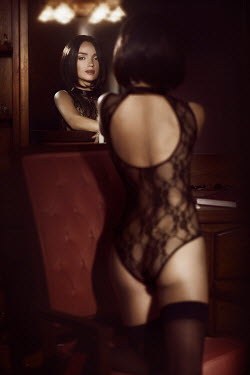 Alex Maxim Sensual boudoir portrait of a sexy woman with short hair, in black lace lingerie, looking in a vanity mirror.