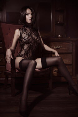 Alex Maxim Sensual boudoir portrait of a seductive woman with short hair, wearing black lingerie and stockings, sitting in a chair in a provocative pose with expressive look.