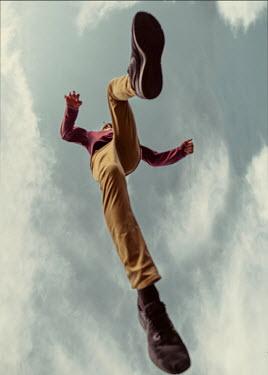Elisabeth Ansley Teenage boy jumping under clouds Men