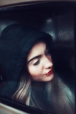 Ildiko Neer Young woman behind wet window