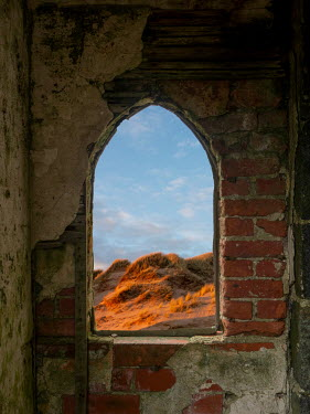 David Baker Grass on sand dunes through brick window of abandoned house Building Detail