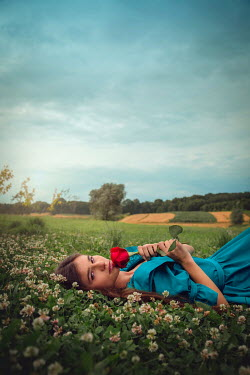 Joanna Czogala Young woman lying in meadow with red rose Women