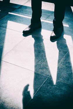 Mohamad Itani Legs of businessman standing on tile floor Men