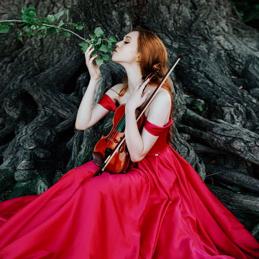 Jovana Rikalo Young woman in red gown sitting on tree with violin Women