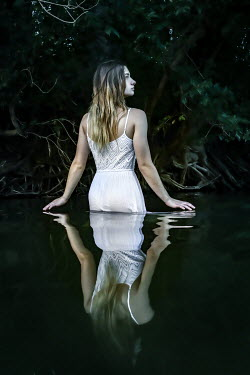 Stephen Carroll REFLECTION OF GIRL IN RIVER WITH TREE ROOTS Women
