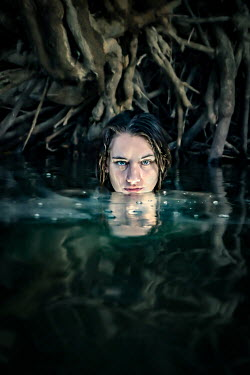 Stephen Carroll REFLECTION OF WOMAN IN RIVER WITH TREE ROOTS Women