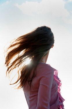 Ute Klaphake BRUNETTE WOMAN WITH FLOWING HAIR IN SUNLIGHT Women