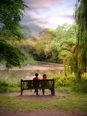 Vesna Armstrong YOUNG COUPLE SITTING ON BENCH BY RIVER Couples