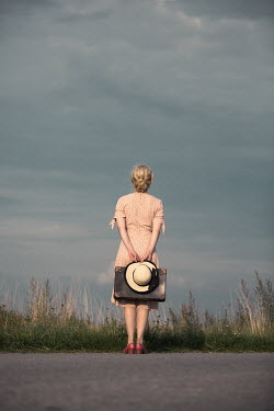 Magdalena Russocka young blonde woman with hat and suitcase standing by country road