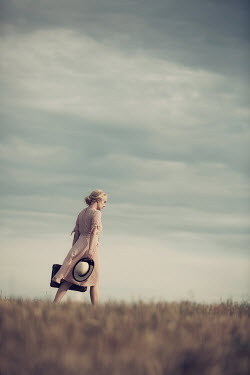 Magdalena Russocka young blonde woman with hat and suitcase walking in field