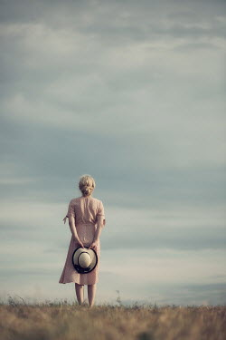 Magdalena Russocka young blonde woman holding hat in her hands standing in field