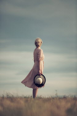 Magdalena Russocka young blonde woman holding hat in her hand standing in field