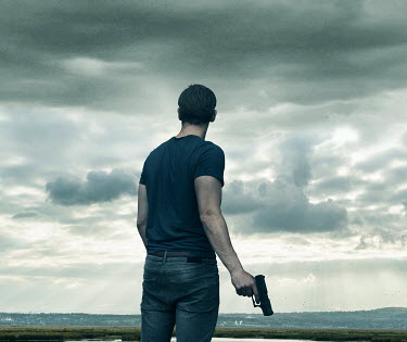 CollaborationJS MAN WITH GUN IN LANDSCAPE FROM BEHIND Men