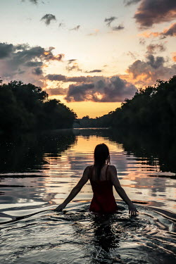 Stephen Carroll WOMAN STANDING IN RIVER AT SUNSET Women