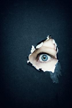 Magdalena Russocka eye peeping through hole in wall