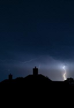 Trevor Payne Lightning above silhouette of house
