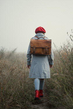 Magdalena Russocka retro teenage girl with school bag walking in misty field