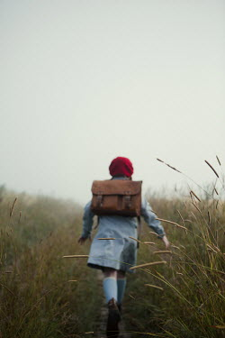 Magdalena Russocka retro teenage girl with school bag running in misty field