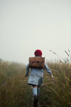 Magdalena Russocka retro teenage girl with school bag running in misty field