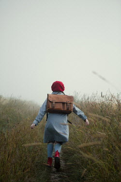 Magdalena Russocka rerto teenage girl with school bag running in misty field