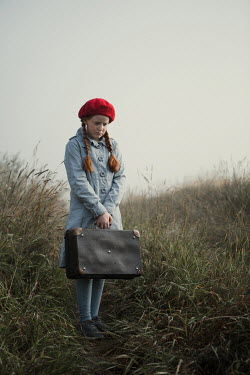 Magdalena Russocka sad young retro girl with suitcase standing in misty field