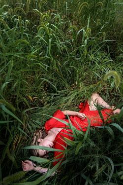 Stephen Carroll woman in red dress laying in greenery Women