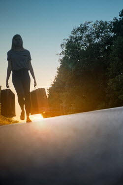 Terry Bidgood Girl walking with suitcases down an empty road Women