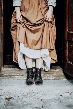 Natasza Fiedotjew Historical woman on doorstep holding skirts in victorian shoes