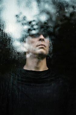 Natasza Fiedotjew Noir close up of man standing behind glass with raindrops