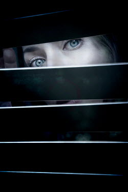 Miguel Sobreira Young woman peering through blinds