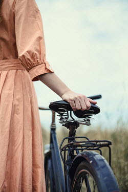 Magdalena Russocka close up of retro woman with bike standing in field
