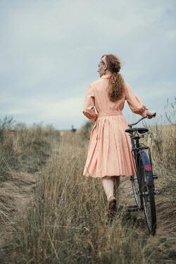 Magdalena Russocka retro woman with bike walking in field