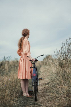 Magdalena Russocka retro woman with bike standing in field Women