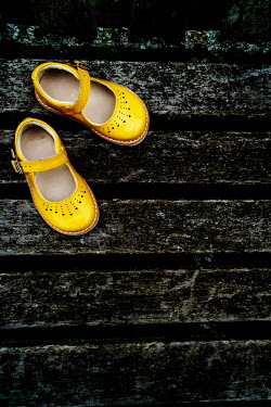Stephen Mulcahey A pair of childs yellow sandals discarded on a park, bench