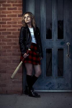 Robin Macmillan Rebellious teenage girl with leather jacket and baseball bat by door