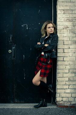 Robin Macmillan Teenage girl in leather jacket standing in doorway